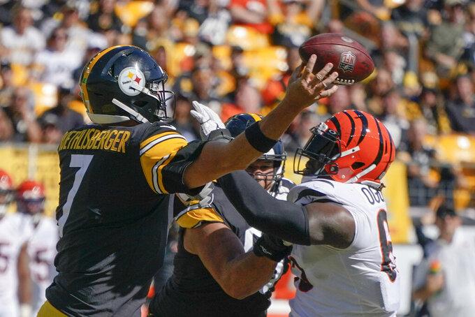 Cincinnati Bengals defensive tackle Larry Ogunjobi (65) hits Pittsburgh Steelers quarterback Ben Roethlisberger (7) as Roethlisberger passes during the second half an NFL football game, Sunday, Sept. 26, 2021, in Pittsburgh. (AP Photo/Gene J. Puskar)