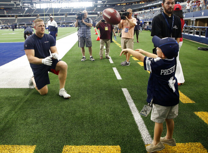 Houston Texans' J.J. Watt, left, tosses a ball with Jarrett Skaggs, 5, of Vega, Texas, before the team's preseason NFL football game against the Dallas Cowboys in Arlington, Texas, Saturday, Aug. 24, 2019. (AP Photo/Michael Ainsworth)