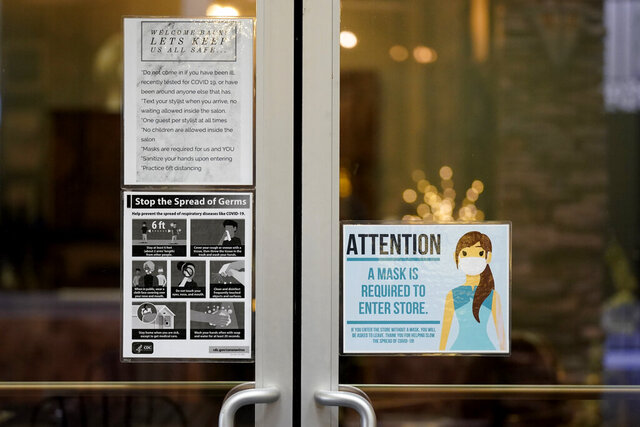 Signs posted on the door of the Luscious Salon advises customers about the pandemic guidelines followed, Lodi, Calif., Wednesday, Dec. 9, 2020. Lodi, a city of just under 68,000 people, is part of the San Joaquin Valley region.  The coronavirus is spreading rapidly in California's San Joaquin Valley and filling its hospitals. It has the fewest available intensive care unit beds of any region in California, a frightening reality that health officials hope will convince more people to wear masks and socially distance.  (AP Photo/Rich Pedroncelli)