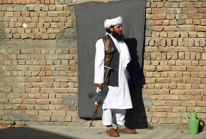 Mofti Noman's house guard stand in front of his home near the mosque after a bomb explosion in Shakar Dara district of Kabul, Afghanistan, Friday, May 14, 2021. A bomb ripped through a mosque in northern Kabul during Friday prayers killing 12 worshippers, Afghan police said. (AP Photo/Rahmat Gul)