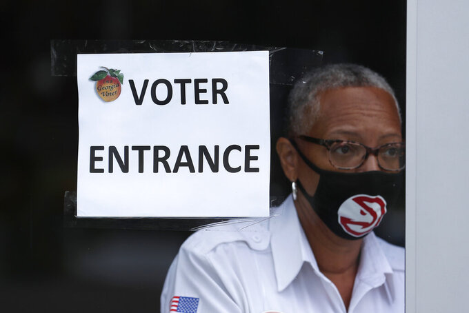 An Atlanta Hawks security guard opens a door before a media tour of the State Farm Arena, home of the NBA's Atlanta Hawks basketball team, Friday, July 17, 2020, in Atlanta. The 16,888-seat facility will be used as a poll location for the upcoming election. (AP Photo/John Bazemore)