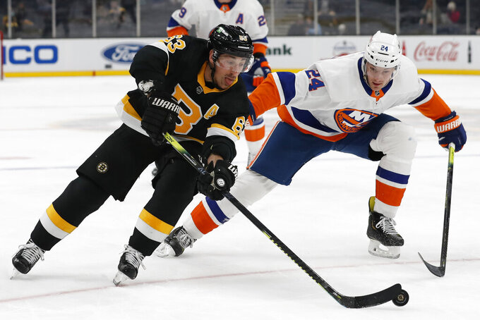 Boston Bruins' Brad Marchand goes around New York Islanders defenseman Scott Mayfield during the first period of an NHL hockey game Friday, April 16, 2021, in Boston. (AP Photo/Winslow Townson)