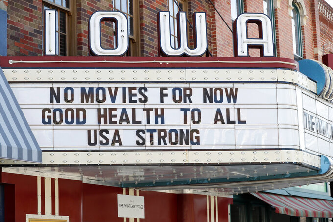 FILE - This Wednesday, April 1, 2020 file photo shows the marquee for the Iowa Theater, closed in response to the COVID-19 coronavirus outbreak, on John Wayne Drive in Winterset, Iowa. The $349 billion program approved by Congress to help small businesses devastated by the coronavirus outbreak is expected to be spent quickly after it opens on Friday, April 3, 2020, in part because large franchisees and multi-property companies are poised to claim a disproportionate share as soon as the money starts flowing. (AP Photo/Charlie Neibergall)