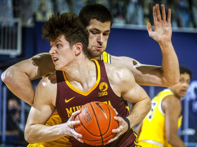 Minnesota center Liam Robbins, front, handles the ball under the basket, defended by Michigan center Hunter Dickinson, back, in the first half of an NCAA college basketball game at Crisler Center in Ann Arbor, Mich., Wednesday, Jan. 6, 2021. (AP Photo/Tony Ding)