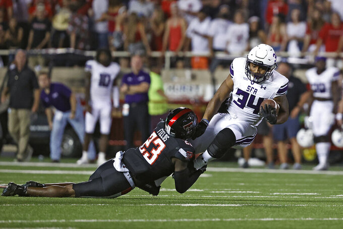 Texas Tech's DaMarcus Fields (23) tackles Stephen F. Austin's Ja'Bray Young (34) during the second half of an NCAA college football game Saturday, Sept. 11, 2021, in Lubbock, Texas. (AP Photo/Brad Tollefson)