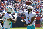 Miami Dolphins quarterback Tua Tagovailoa, right, passes the ball to running back Myles Gaskin during the first half of an NFL preseason football game against the Chicago Bears in Chicago, Saturday, Aug. 14, 2021. (AP Photo/Nam Y. Huh)