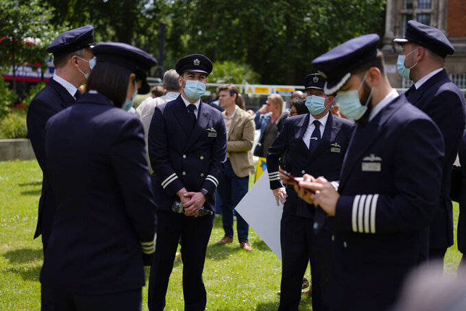 British Airways flight take part in a 'Travel Day of Action' protest across the street from the Houses of Parliament in London, Wednesday, June 23, 2021. The protest on Wednesday was attended by people from across the UK aviation and travel industry calling on the British government to safely reopen international travel for the peak summer season to protect travel jobs and businesses amidst Britain's widely praised rollout of coronavirus vaccines. (AP Photo/Matt Dunham)