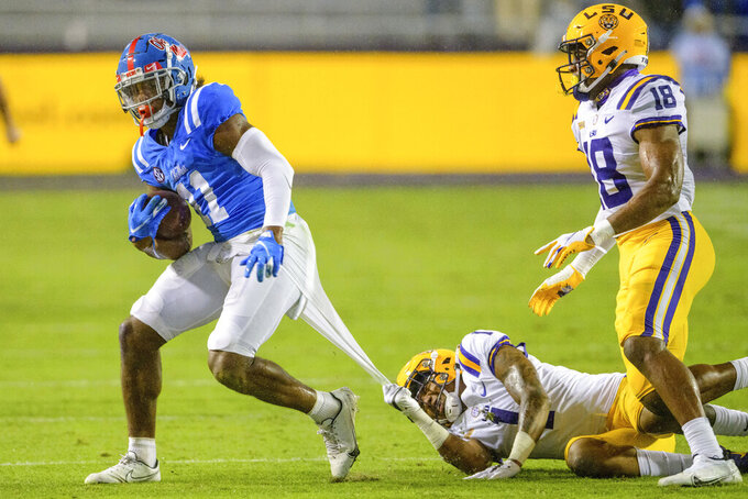 Mississippi wide receiver Dontario Drummond (11) runs away from a shirt-tackle by LSU cornerback Eli Ricks (1) during the second half of an NCAA college football game in Baton Rouge, La., Saturday, Dec. 19, 2020. (AP Photo/Matthew Hinton)