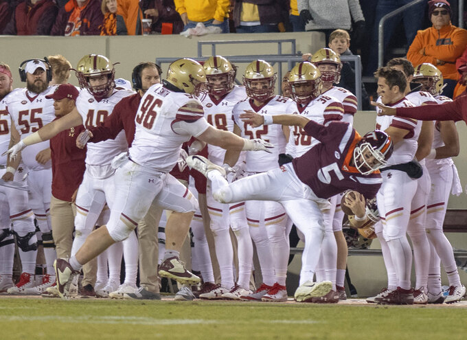 Virginia Tech quarterback Ryan Willis is shoved out of bounds by Boston College's Ray Smith during an NCAA college football game in Blacksburg, Va., Saturday, Nov. 3, 2018. (AP Photo/Matt Bell)