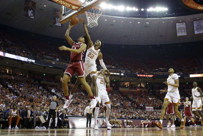 Oklahoma forward Jalen Hill (1) scores past Texas forward Kai Jones (22) during the first half of an NCAA college basketball game in Austin, Texas, Wednesday, Jan. 8, 2020. (AP Photo/Eric Gay)