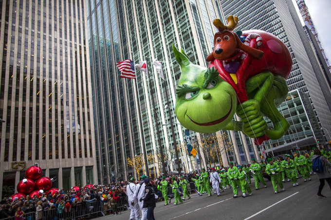 FILE - In this Nov. 28, 2019 file photo, the Grinch balloon floats down Sixth Avenue during the Macy's Thanksgiving Day Parade in New York.  The Macy's Thanksgiving Day Parade will return to New York City's streets this year with COVID-19 protocols including a vaccination requirement for parade volunteers. Macy's says the Nov. 25, 2021 parade will be broadcast on NBC and will feature the traditional giant balloons, celebrity performers, clowns and marching bands.  (AP Photo/Eduardo Munoz Alvarez, file)