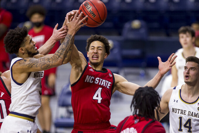 Notre Dame's Prentiss Hubb, left, competes for a rebound with North Carolina State's Jericole Hellems (4) during the first half of an NCAA college basketball game Wednesday, March 3, 2021, in South Bend, Ind. North Carolina State won 80-69. (AP Photo/Robert Franklin)