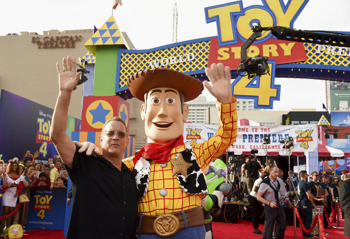 Tom Hanks, left, poses with his character Woody as he arrives at the world premiere of