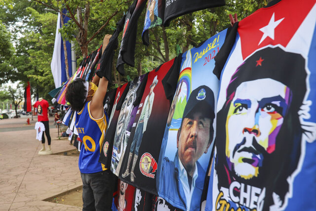 A vendor sells T-shirts promoting Nicaraguan President Daniel Ortega and The Sandinista National Liberation Front ruling party on the sidelines of a new monument, called the Peace Bell, before its inauguration ceremony later in the day in Managua, Nicaragua, Friday, July 17, 2020. Nicaraguan President Daniel Ortega's government is being deterred by the new coronavirus from holding the usual mass celebration to mark the victory of the country's revolution July 19, and will instead unveil a new addition to its collection of monuments. At right is a T-shirt of Cuba's revolutionary hero Ernesto