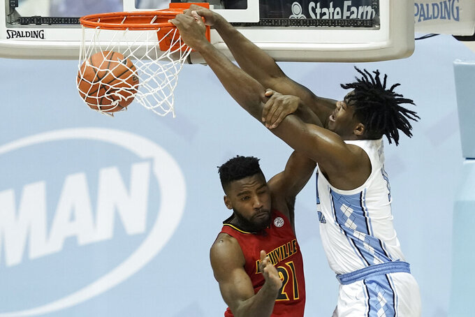 North Carolina forward Day'Ron Sharpe, right, dunks against Louisville guard Charles Minlend (21) during the second half of an NCAA college basketball game in Chapel Hill, N.C., Saturday, Feb. 20, 2021. (AP Photo/Gerry Broome)