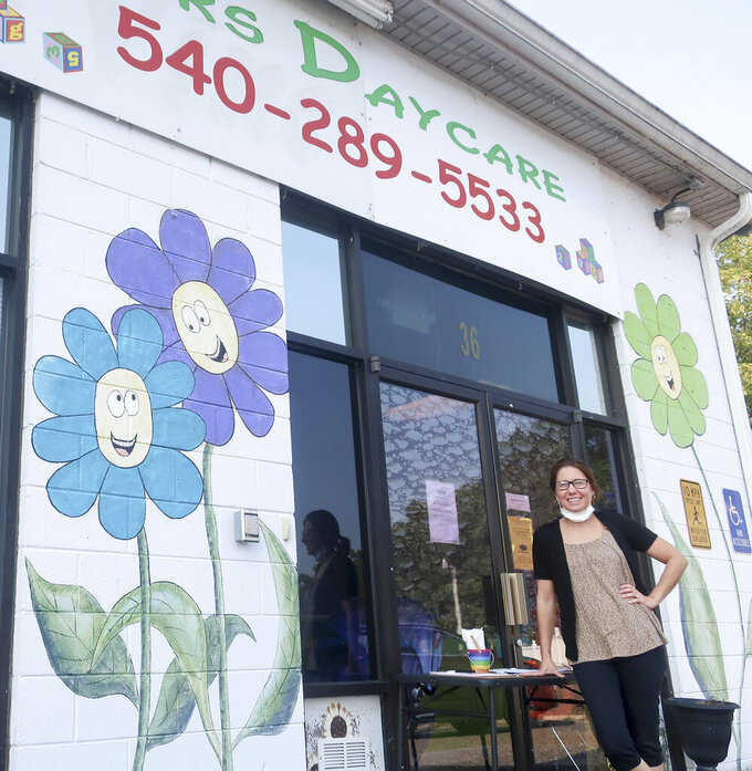 In this Sept. 13, 2021 photo, Toni Bowyer, long-time director of Lil' Bloomers Daycare in McGaheysville, Va., poses for a photograph outside of the center's entrance. (Ian Munro/Daily News-Record via AP)