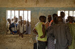 People peer through a window as party agents huddle together to watch votes being counted inside a polling station in Kano, northern Nigeria Saturday, Feb. 23, 2019. Nigerians went to the polls for a presidential election Saturday, one week after a surprise delay for Africa's largest democracy. (AP Photo/Ben Curtis)
