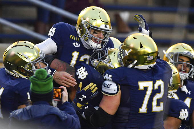 Notre Dame quarterback Ian Book (12) celebrates after running for a touchdown in the second half of an NCAA college football game Saturday, Dec. 5, 2020, in South Bend, Ind. (Matt Cashore/Pool Photo via AP)
