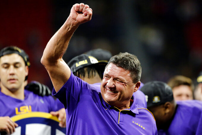 FILE - In this Dec. 7, 2019, file photo, LSU coach Ed Orgeron celebrates on stage after the team's win over Georgia in an NCAA college football game for the Southeastern Conference championship, in Atlanta. Cajun pride is swelling in Lafourche Parish now that the former two-way football standout who won a 1977 state title for the South Lafourche High School Tarpons is on the brink of capping off arguably the LSU Tigers' greatest season in the program's 126-year history with a national title. (C.B. Schmelter/Chattanooga Times Free Press via AP, File)