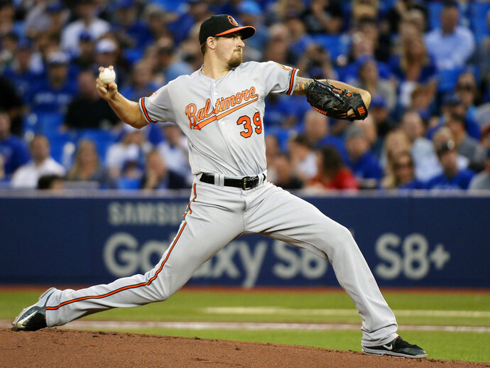 FILE - In this Sept. 13, 2017, file photo, Baltimore Orioles starting pitcher Kevin Gausman (39) works against the Toronto Blue Jays during the first inning of a baseball game in Toronto. The Orioles avoided an arbitration hearing with pitcher Kevin Gausman, agreeing to a $5.6 million, one-year contract. The agreement was made Tuesday, Feb. 13, 2018. (Nathan Denette/The Canadian Press via AP, File)