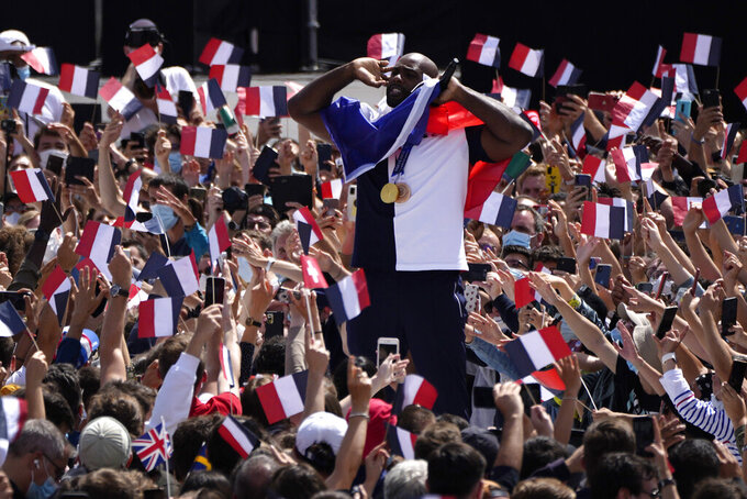 French Olympic heavyweight bronze medallist and mixed team gold medallist in Judoka, Teddy Riner, center, is wrapped in a French flag as he cheers on fans in the Olympics fan zone at Trocadero Gardens in front of the Eiffel Tower in Paris, Sunday, Aug. 8, 2021. A giant flag will be unfurled on the Eiffel Tower in Paris Sunday as part of the handover ceremony of Tokyo 2020 to Paris 2024, as Paris will be the next Summer Games host in 2024. The passing of the hosting baton will be split between the Olympic Stadium in Tokyo and a public party and concert in Paris. (AP Photo/Francois Mori)