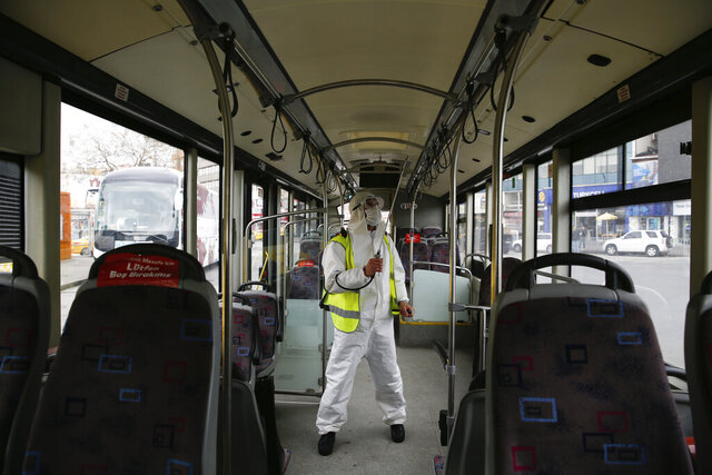 A municipality worker wearing a protective suit sprays disinfectant on a bus in Istanbul, amid the coronavirus outbreak, Friday, April 3, 2020. The new coronavirus causes mild or moderate symptoms for most people, but for some, especially older adults and people with existing health problems, it can cause more severe illness or death. (AP Photo/Emrah Gurel)