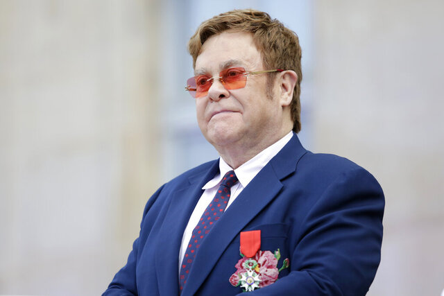 "FILE - This June 21, 2019 file photo shows Elton John at a ceremony honoring him with the Legion of Honor in Paris. John is hosting a ""living room"" concert aimed at bolstering American spirits during the coronavirus crisis and saluting those countering it. The event was announced Wednesday by iHeartMedia and Fox. Alicia Keys, Billie Eilish, Mariah Carey, the Backstreet Boys, Tim McGraw and Billie Joe Armstrong are scheduled to take part in the concert airing at 9-10 p.m. Eastern Sunday on Fox TV and on iHeartMedia radio stations. (AP Photo/Lewis Joly, Pool, File)"