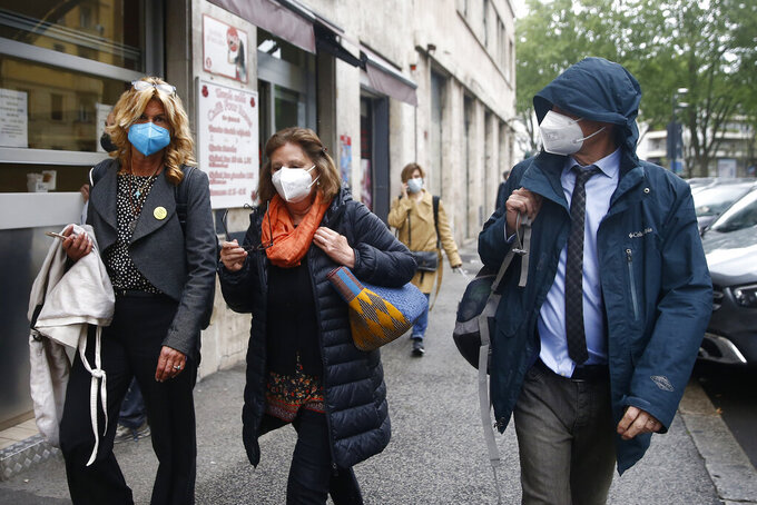 Paola e Claudio Regeni with their lawyer Alessandra Ballerini, left, walk outside the courthouse in Rome, Thursday, April 29, 2021. A judge in Rome on Thursday postponed a hearing to decide if four high-ranking members of Egypt's security forces should go on trial for the abduction, torture and killing in Cairo of an Italian doctoral student. In December, Italian prosecutors, who are seeking trial indictment, formally put the four Egyptians under investigation for their alleged roles in the 2016 slaying of Giulio Regeni. (Cecilia Fabiano/LaPresse via AP)