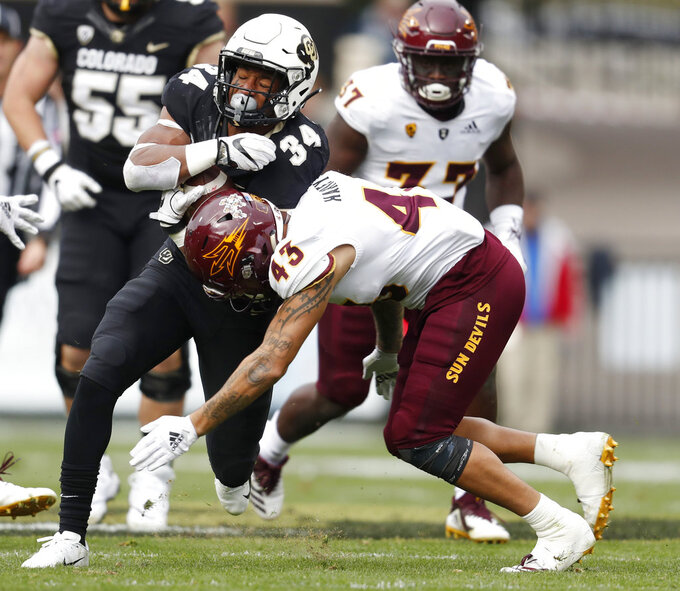 Colorado running back Travon McMillian, left, is tackled by Arizona State safety Jalen Harvey in the second half of an NCAA college football game Saturday, Oct. 6, 2018, in Boulder, Colo. Colorado won 28-21. (AP Photo/David Zalubowski)