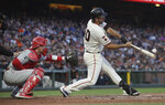 San Francisco Giants' Madison Bumgarner hits a single in front of Philadelphia Phillies catcher Andrew Knapp during the third inning of a baseball game in San Francisco, Thursday, Aug. 8, 2019. (AP Photo/Jeff Chiu)