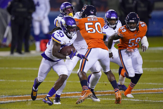 Minnesota Vikings running back Dalvin Cook (33) runs with the ball as Chicago Bears linebacker Barkevious Mingo (50) and linebacker Danny Trevathan (59) defend during the first half of an NFL football game Monday, Nov. 16, 2020, in Chicago. (AP Photo/Nam Y. Huh)