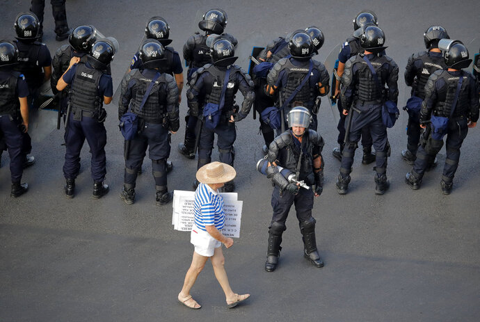 A protester walks by a riot police line outside the government headquarters, in Bucharest, Romania, Friday, Aug. 10, 2018. Romanians who live abroad have begun an anti-government protest calling on the left-wing government to resign and an early election. The expatriates, some of whom drove across Europe for the demonstration, are angry about the Romania is governed. (AP Photo/Vadim Ghirda)