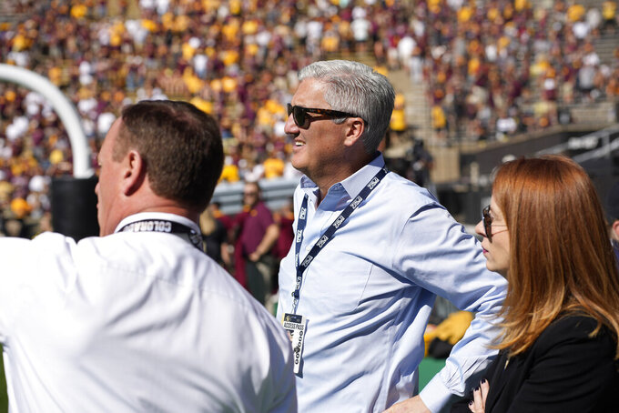Pac-12 commissioner George Kliavkoff, center, joins Colorado athletic director Rick George in the first half of an NCAA college football game Saturday, Sept. 18, 2021, in Boulder, Colo. (AP Photo/David Zalubowski)