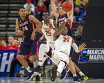 Maryland 's Bruno Fernando (23) passes the ball as he falls in front of Belmont's Michael Benkert (24) during the second half of the first round men's college basketball game in the NCAA Tournament in Jacksonville, Fla., Thursday, March 21, 2019. (AP Photo/Stephen B. Morton)