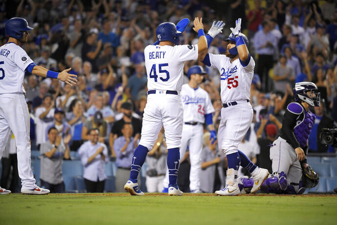 Los Angeles Dodgers' Russell Martin (55) is congratulated by Matt Beaty (45) and Cody Bellinger, left, after hitting a three-run home run, as Colorado Rockies catcher Tony Wolters kneels at the plate during the seventh inning of a baseball game Tuesday, Sept. 3, 2019, in Los Angeles. (AP Photo/Mark J. Terrill)