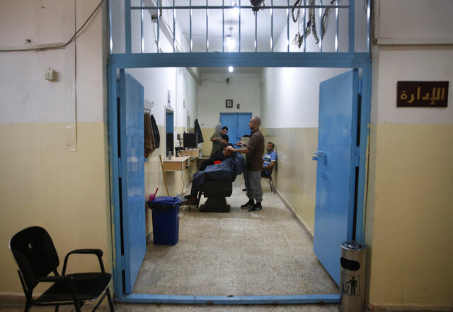 CAPTION ADDITION: ADDS DETAILS ABOUT WHICH PRISON HAD RIOTS: FILE - In this April 3, 2018, file photo, prisoners cut the hair of other inmates in the barber shop of a Kurdish-run prison housing former members of the Islamic State group, in Qamishli, north Syria. A spokesman for Kurdish-led forces in northeastern Syria said Monday, March. 30, 2020 they have put an end to riots by Islamic State militants in a prison there. The riots broke out late on Sunday in a prison in the town of Hassakeh and lasted several hours. Kurdish authorities run more than two dozen detention facilities scattered around northeastern Syria, holding about 10,000 IS fighters. (AP Photo/Hussein Malla, File)