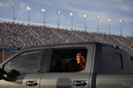 Graduate Maggie Whipple sits in the back of a truck during a drive-thru graduation for Faith Lutheran High School at the Las Vegas Motor Speedway, Friday, May 22, 2020, in Las Vegas. The school held a special drive-thru graduation amid the coronavirus pandemic. (AP Photo/John Locher)