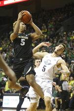 Colorado's D'Shawn Schwartz, left, shoots over Oregon's Chris Duarte during the second half of an NCAA college basketball game in Eugene, Ore., Thursday, Feb. 13, 2020. (AP Photo/Chris Pietsch)