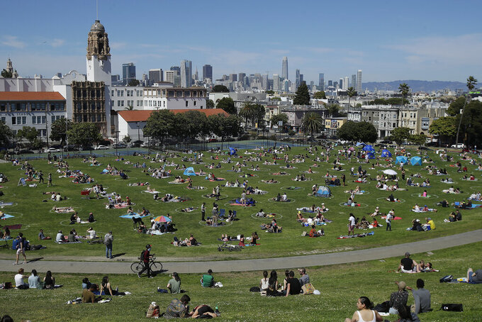 FILE - In this May 24, 2020, file photo, visitors set up inside circles designed to help prevent the spread of the coronavirus by encouraging social distancing at Dolores Park in San Francisco. Los Angeles and San Francisco are poised Tuesday, May 4, 2021, to be the only major urban areas in the state to meet guidelines to move into the least-restrictive tier, amid the pandemic. It's a remarkable turnaround considering California was the epicenter of the virus outbreak in the U.S. just a few months earlier. (AP Photo/Jeff Chiu, File)