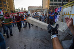 Anti-government protesters remove a concrete wall that was installed by security forces to prevent them from reaching the government palace in Beirut, Lebanon, Thursday, July 2, 2020. Major retailers in Lebanon announced Thursday they will temporarily close in the face of an increasingly volatile currency market and their inability to set prices while the local currency tumbles before the dollar. (AP Photo/Hassan Ammar)