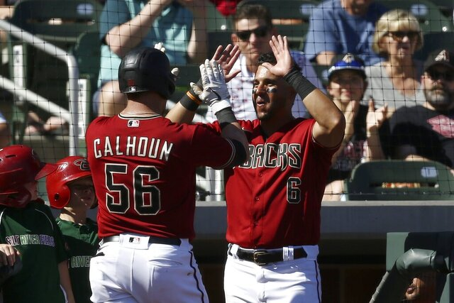 Arizona Diamondbacks' Kole Calhoun (56) celebrates his two-run home run against the Kansas City Royals with teammate David Peralta (6) during the fourth inning of a spring training baseball game Monday, March 9, 2020, in Scottsdale, Ariz. (AP Photo/Ross D. Franklin)