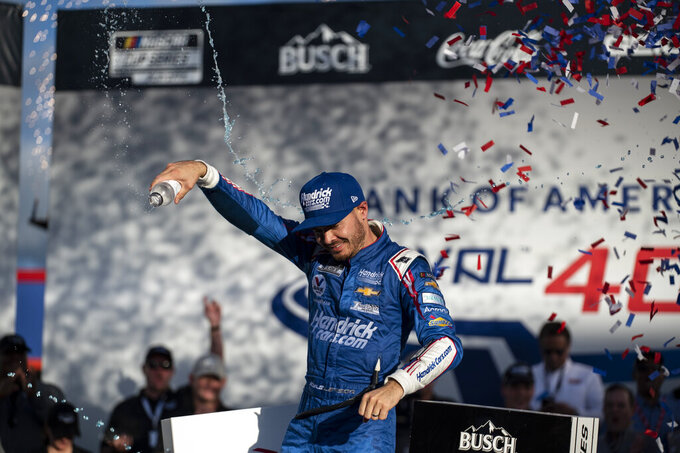Kyle Larson celebrates in Victory Lane after winning a NASCAR Cup Series auto racing race at Charlotte Motor Speedway, Sunday, Oct. 10, 2021, in Concord, N.C. (AP Photo/Matt Kelley)