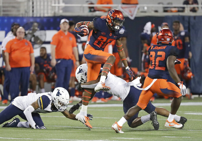 Syracuse wide receiver Taj Harris, center, leaps over West Virginia safety Dravon Askew-Henry after a reception during the first half of the Camping World Bowl NCAA college football game Friday, Dec. 28, 2018, in Orlando, Fla. (AP Photo/John Raoux)