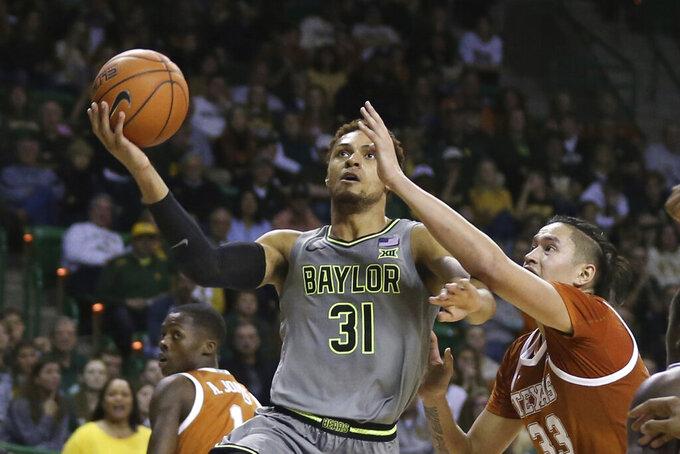 Baylor guard MaCio Teague, left, shoots over Texas forward Kamaka Hepa, right, in the second half of an NCAA college basketball game, Saturday, Jan. 4, 2020, in Waco, Texas. Baylor won 59-44. (AP Photo/Rod Aydelotte)