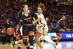 File-This March 6, 2020, file photo shows Georgia's Jenna Staiti (14) dribbling while defended by South Carolina's Mikiah Herbert-Harrigan during a quarterfinal match at the Southeastern women's NCAA college basketball tournament in Greenville, S.C. The Georgia Lady Bulldogs are back in the Top 25. Staiti leads the team in scoring at 14.2 points a game, but seven other players are averaging at least 5.5 points. Even more telling, 10 players are averaging double-digit minutes per night. (AP Photo/Richard Shiro, File)