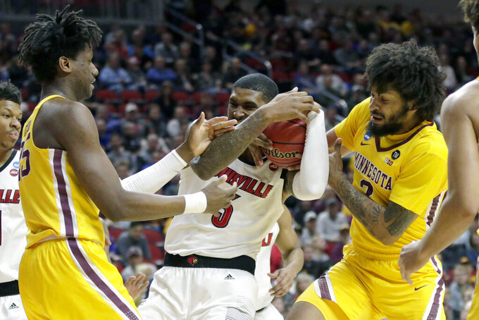 Minnesota's Daniel Oturu, left, and Jordan Murphy (3) struggle for the ball with Louisville's Malik Williams (5) during the first half of a first round men's college basketball game in the NCAA Tournament, in Des Moines, Iowa, Thursday, March 21, 2019. (AP Photo/Nati Harnik)