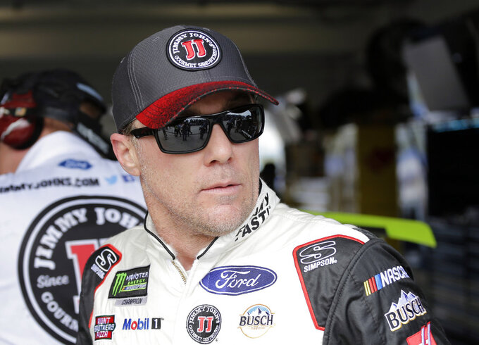Kevin Harvick walks in the garage during qualifying for the NASCAR Cup Series auto race at the Homestead-Miami Speedway, Saturday, Nov. 17, 2018, in Homestead, Fla. (AP Photo/Terry Renna)