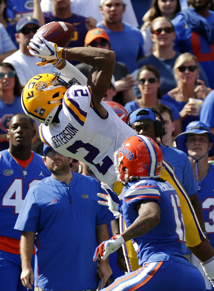LSU wide receiver Justin Jefferson (2) catches a pass over Florida defensive back C.J. McWilliams, right, during the first half of an NCAA college football game, Saturday, Oct. 6, 2018, in Gainesville, Fla. (AP Photo/John Raoux)