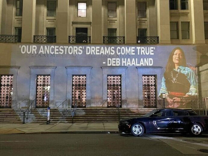 This photo provided by Leah Salgado shows the image of New Mexico U.S. Rep. Deb Haaland projected on the side of the U.S. Department of the Interior building in Washington, D.C., on Monday, Feb. 22, 2021. Native Americans will be closely watching a confirmation hearing Tuesday, Feb. 23, 2021, for Haaland, who has been nominated to lead the Interior Department. If confirmed, she would be the first Native American to lead the agency that has broad oversight of tribal affairs and energy development. (Leah Salgado via AP)