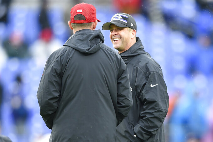 Baltimore Ravens head coach John Harbaugh, right, talks with San Francisco 49ers head coach Kyle Shanahan, left, on the field before the start of the first half of an NFL football game, Sunday, Dec. 1, 2019, in Baltimore, Md. (AP Photo/Gail Burton)